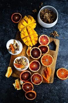 Zdrowy deser jogurtowy z granolą, orzeszkami, pomarańczami i mango